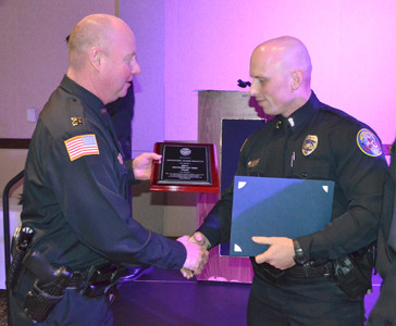 OFFICER JOSH HODGE, right, received the 2017 Officer of the Year award at the recent Cleveland Police Department awards luncheon. Presenting the award is Capt. Stacy Smith.