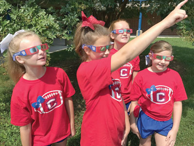 Gincy Pendergrass, center, is shown here pointing out where the Great Eclipse will take place on Aug. 21. She's informing friends at Cleveland Middle School, Olivia Lefoy, Madilyn Maselli and Reece Meagher. Cleveland businessman Allan Jones donated 40,000 pairs of special eclipse glasses to students in six school systems.