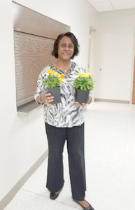 Edwina Robinson, hostess and president, poses with her container pots of marigolds and daisies at the June meeting of Aldersgate Garden Club.