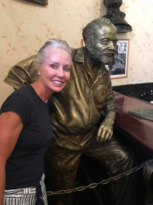Janie Jones poses with the statute of legendary writer Ernest Hemingway at the Floridita restaurant which Hemingway frequented.