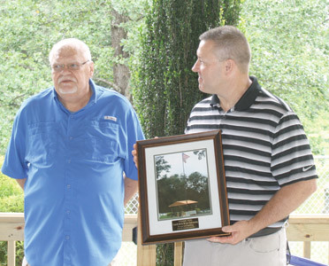 KIM DEESE, left, presented Lee University baseball coach Mark Brew with a commemorative photograph this week for his support of local veteran organizations through his and Lee's annual Military Appreciation Day.
