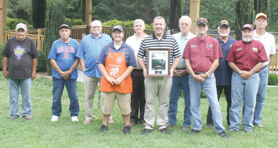 "LEE UNIVERSITY baseball coach Mark Brew (at center, holding photograph) was honored this week by representatives of local veteran organizations, for his support of a number of local vets' programs. At the presentation at the veterans' section of Fort Hill Cemetery were, from left, Paul Goins, Bobby ""Bullet"" Goins, Kim Deese, Courtney Webb of The Home Depot, Veterans Affairs Officer Joe Davis, Brew, Cid Heidel, Bill Gray, Doug Ayers, Glenn Slaughter and John Thomason. Funds from the 2016 program went to the Disabled American Veterans for construction of the pavilion in the background."