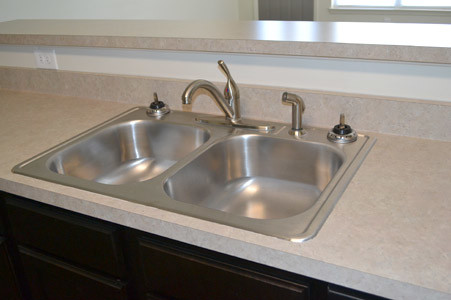 ALL OF THE APARTMENTS feature many amenities, including the stainless steel kitchen sink, which faces living room.