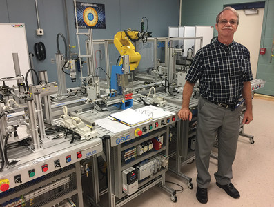 Charlie Womac, CSCC's associate professor of industrial technology, stands in front of the FMS 200 Mechatronics equipment.