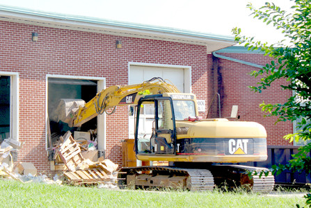 A WORKER scoops debris from one of the loading areas of the former American Uniform building, which is being turned into a Bradley County Schools facility. Tons of debris were hauled away from the building on Friday and Saturday.