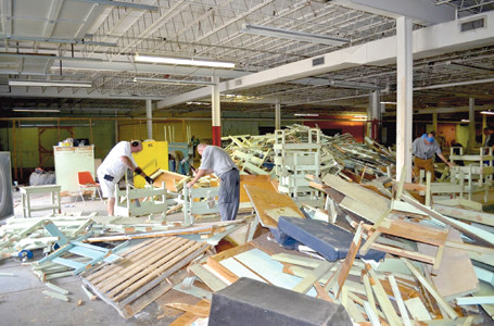 WORKERS break apart old shelves used inside the former American Uniform building recently bought by Bradley County Schools. Santek Waste Services and Wright Brothers Construction cleaned out the facility for the school system Friday and Saturday.