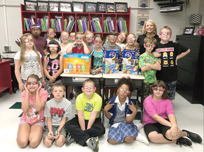STUDENTS in Trena Johnson's fourth-grade class at Oak Grove Elementary School show off the solar eclipse viewing glasses they received Friday. They also enjoyed some specially-themed snacks — Moon Pies and Sun Chips.