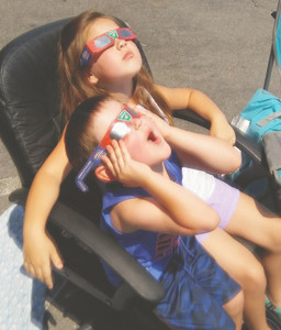 NICHOLAS AND KATELYN GUY stare into the solar eclipse in amazement from the parking lot of the Cleveland Daily Banner, where employees gathered to watch the show.