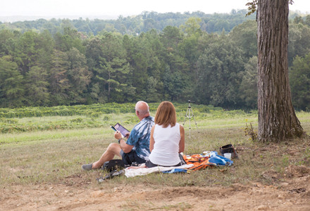 A COUPLE RELAXES while waiting for the solar eclipse to reach totality at the Cleveland/Bradley Chamber of Commerce Solar Sip & See event at Morris Vineyard.