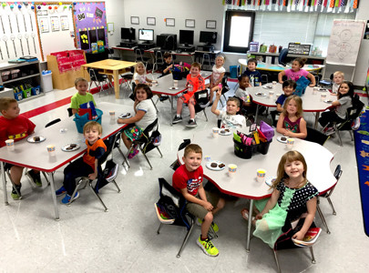 KINDERGARTENERS in Allison Bacon's class at Waterville Community Elementary celebrated the Aug. 21, 2017, solar eclipse after returning to school the next day. They did a writing activity where they needed to explain what they saw when they watched the eclipse. Here, they are enjoying eclipse-themed snacks: Sunny D, Cosmic Brownies and MoonPies.