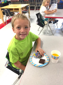 NOLAN LIGHT, a kindergarten student at Waterville Community Elementary, enjoys a snack with classmates in Allison Bacon's class. While learning about the Aug. 21, 2017, solar eclipse, they enjoyed Moon Pies, Cosmic Brownies and Sunny D drinks.