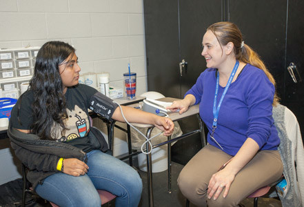 JESSICA CASTILLO, left, gets her blood pressure checked by volunteer Cortney Ruiz at the CMS health fair.