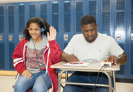 ISABELLA BLAIR, left, raises her hand as an indicator that she is hearing out of her left ear during this screening performed by volunteer Rodney Broadnax.