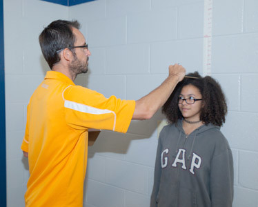 K-TIA BAILEY, right, stands tall for her height and weight screening performed by Coach Eric Frazier.