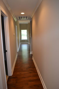 ONCE YOU ENTER the home, you see this nice hardwood-floor hallway leading to the living room, kitchen and dining areas.