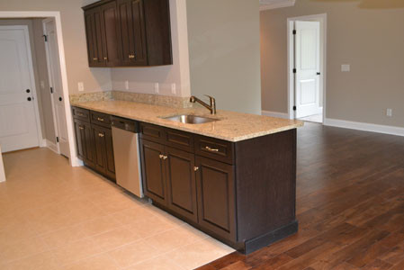 GRANITE COUNTERTOPS are a special feature in the kitchen area, below, along with beautiful wooden cabinets and a spacious sink.