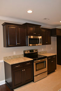 STAINLESS STEEL APPLIANCES grace the kitchen area, featuring a Kenmore oven/range, microwave oven and dishwasher.
