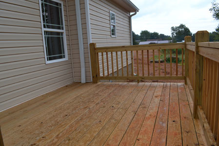 A BEAUTIFUL DECK is at the rear of the home, and is perfect for placing a grill and furniture to enjoy the sunrise or sunset.