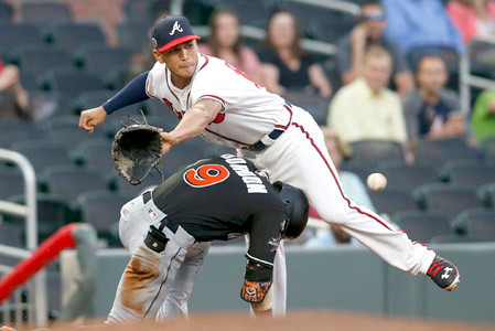 Atlanta Braves third baseman Rio Ruiz, top, reaches for a ball as Miami Marlins' Dee Gordon (9) slides in safely for a triple in the first inning of a baseball game, Thursday, Sept. 7, 2017, in Atlanta. (AP Photo/Brett Davis)