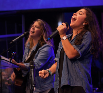 KAYLEE, left, and Erica Tuttle lead the opening band at the Cry Out America prayer event on Monday.