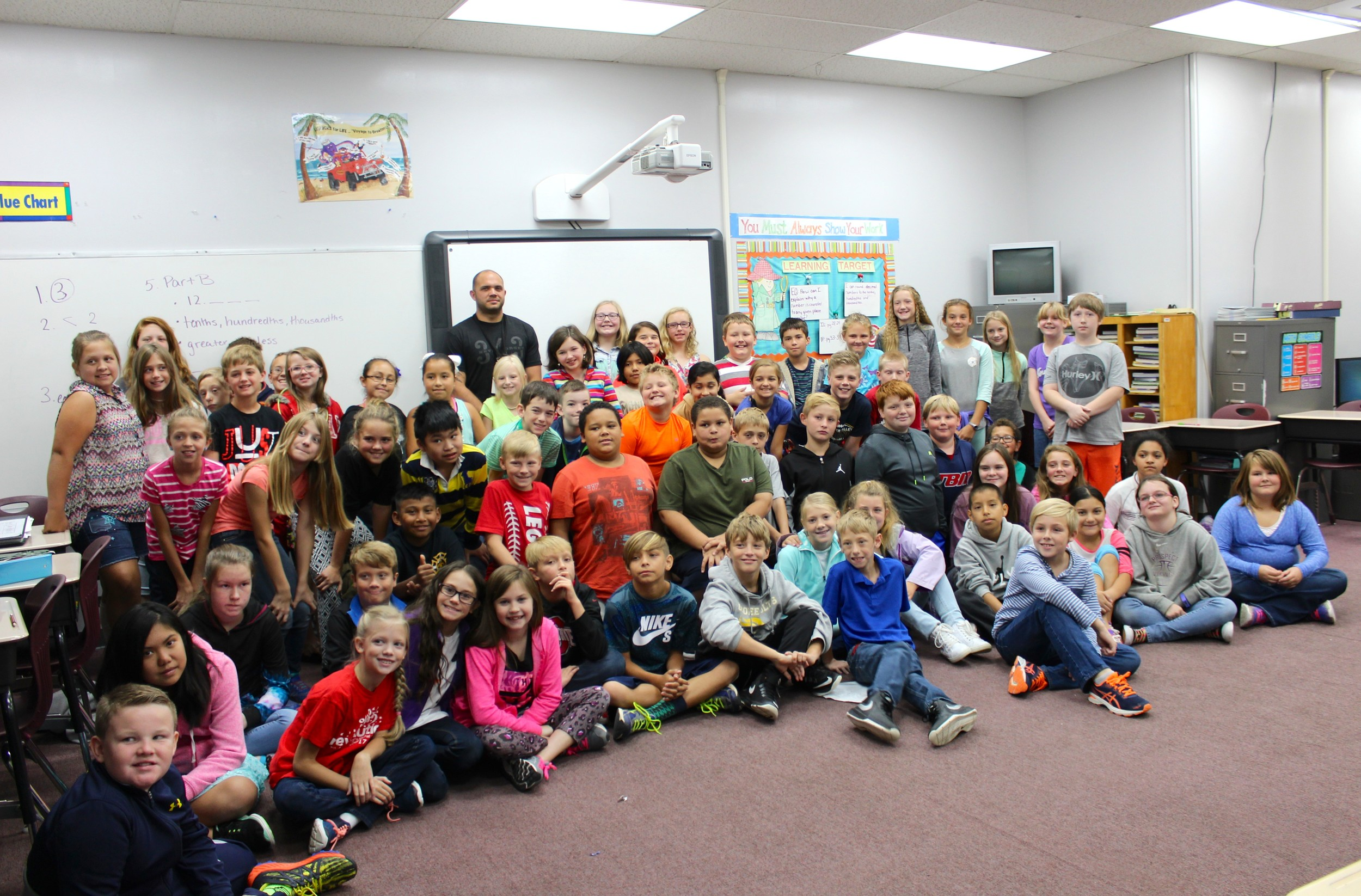 AARON HICKS, a local firefighter and EMT, joins a group of fifth-graders at Prospect Elementary School for a photo. He spoke to the students Monday about the sacrifices firefighters made while responding to the terrorist attacks on Sept. 11, 2001.
