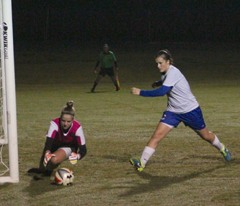 CLEVELAND SENIOR goal keeper Lauren Stutzman, left, dives to prevent a shot late in the game, as Madison Dasher looks. The action came during a District 5-AAA tilt with McMinn County. The Lee University soccer commit finished with a season's best 17 saves.