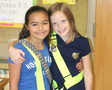 SHIANNE KIMMONS, left, and Grace Sadler, right, were two of the fifth-grade safety patrol members who greeted Blythe-Bower guests for Star Spangled Banner Day.