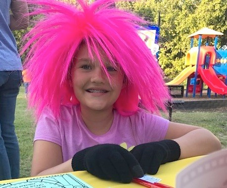 "SHOWING OFF some bright, spiky hair, a costumed student enjoys the festivities during the recent family movie night hosted by the Michigan Avenue School PTO. Students showed up dressed as rock stars to watch the movie ""SING."""