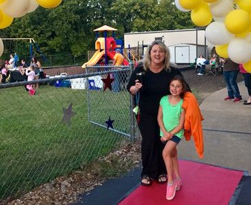 FOURTH-GRADE TEACHER Debbie Walker enjoyed walking down the red carpet under an arch of popcorn at the Michigan Avenue School PTO's Family Movie Night. She is joined by first-grader MacLayne Edgeworth.