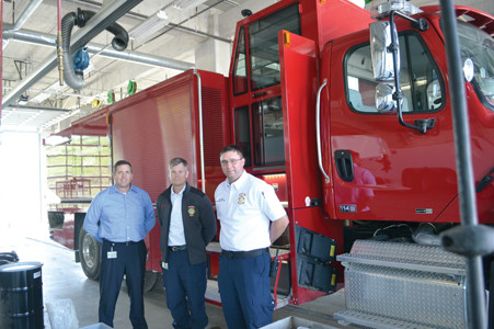 WACKER FIRE DEPARTMENT officials show the size of the Turbo fire truck at the Charleston plant. The Turbo truck is reportedly the only one of its kind in the United States. From left are Tim Sloan, Dan King and Michael Shillings.