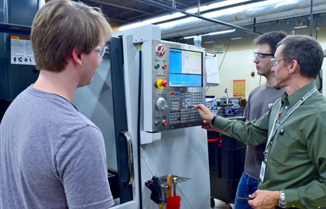 MACHINING STUDENTS Zach Keller, left, and Ryan Caldwell work with teacher Shawn Williams to program the HAAS CNC mill at Bradley Central High School. A grant awarded to Bradley County Schools will add a miniature mill at both county schools.