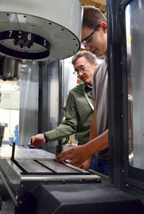 SHAWN WILLIAMS, a teacher at Bradley Central High School, and student Ryan Caldwell program the HAAS CNC mill at Bradley Central High School.