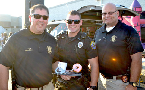 THE WINNING DOUGHNUT eating duo from the Cleveland Police Department defeated the Bradley County Sheriff's Office at Tuesday's National Night Out event. With CPD Chief Mark Gibson, far left, and the winners' trophy are Officer Bradley Colbaugh, center, and Detective Bill Parks.