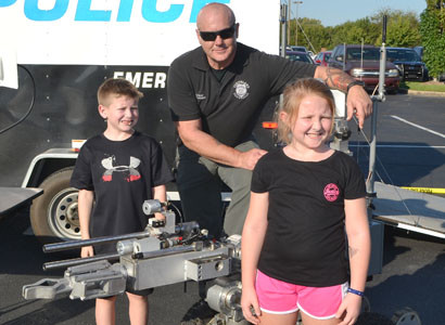 CLEVELAND POLICE OFFICER Victor Cleveland shows off the department's bomb dismantling machine at the National Night Out event to Kambria Charles, foreground, and Tryson Charles