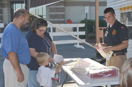 THE CLEVELAND FIRE DEPARTMENT was present at Tuesday's National Night Out, with Fire Inspector Craig Foote passing out information to children and adults. Silas Randolph was excited about meeting the fireman. He was joined by grandparents Baron and Tammy Randolph.