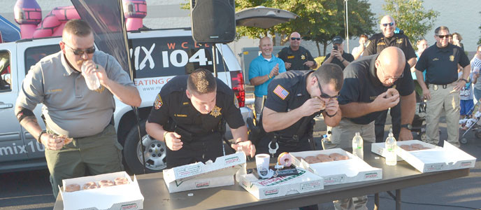 DEPUTY DAVID HARPER shows off his doughnut-eating technique in Tuesday night's contest, but, unfortunately, he and fellow Deputy Jeff Wagner of the Bradley County Sheriff's Office lost the contest to Detective Bill Parks and Officer Bradley Colbaugh of the Cleveland Police Department.