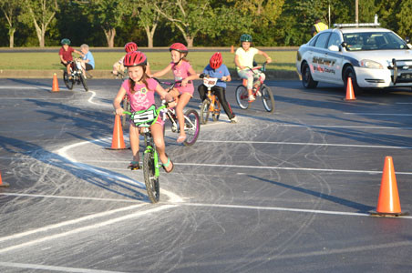 SEVERAL CHILDREN, below, took part in the bicycle course set up at Tuesday's National Night Out at Bradley Square Mall.