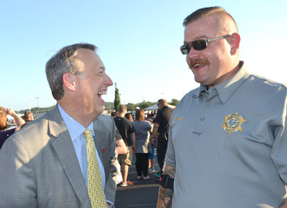 DISTRICT ATTORNEY GENERAL Steve Crump, left, gets some tips about eating doughnuts from Bradley County Sheriff's Office Deputy David Harper following Tuesday night's doughnut-eating competition pitting the BCSO against the Cleveland Police Department.