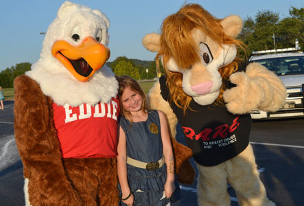 ASHLYN SHILLINGS had fun meeting law enforcement mascots Eddie Eagle, left, and Darren the Lion, at the National Night Out event.