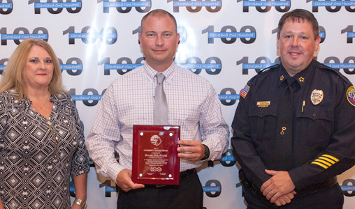 Janey Patten, left, and CPD Mark Gibson, right, present an award to Detective Andy Ratcliff.