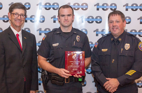 Stephen Crass, left, and Cleveland Police Chief Mark Gibson, right, present an award to CPD Officer Erik Jones.