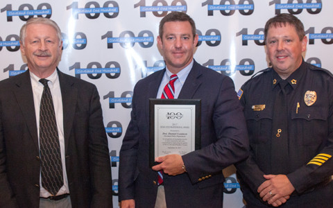 Joe Wilson, left, and CPD Chief Mark Gibson, right, present and award to Detective Daniel Leamon.