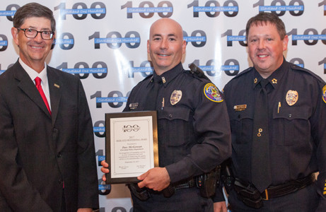 Stephen Crass, left, and Cleveland Police Chief Mark Gibson, right, present an award to CPD Officer Dax McGowan.