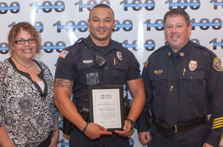 Angie Underwood, left, and Cleveland Police Chief Mark Gibson, right, present an award to CPD Officer Justin West.