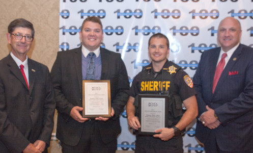 Stephen Crass, left, and Sheriff Eric Watson, right, present awards to BCSO Deputies Will Carter and Tyler Allen.