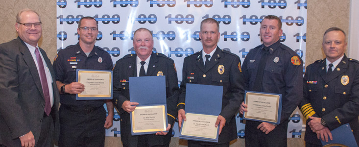 Kelvin Bishop, right, and CFD Chief Ron Harrison, left, present awards to Engineer Josh Woods, Lt. Bill Durgin, Lt. Henley Ledford, and Firefighter Drew Rader.