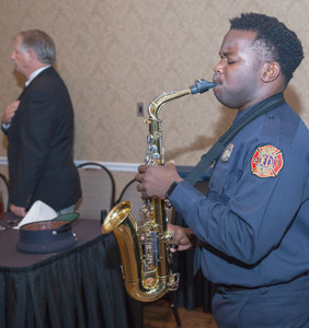 Cleveland Firefighter Sammy Previlus plays the national anthem on the saxophone.