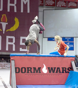Students jump over the final obstacle in the obstacle course race during Dorm Wars 2016.