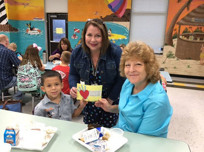 AIMEE PASSAVANT'S kindergarten class presented grandparents with a kissing hand card during the Grandparent Breakfast at Hopewell Elementary School. Here, student Kamden Estrada presents a card to his grandmother. Joining them is Ms. Passavant.