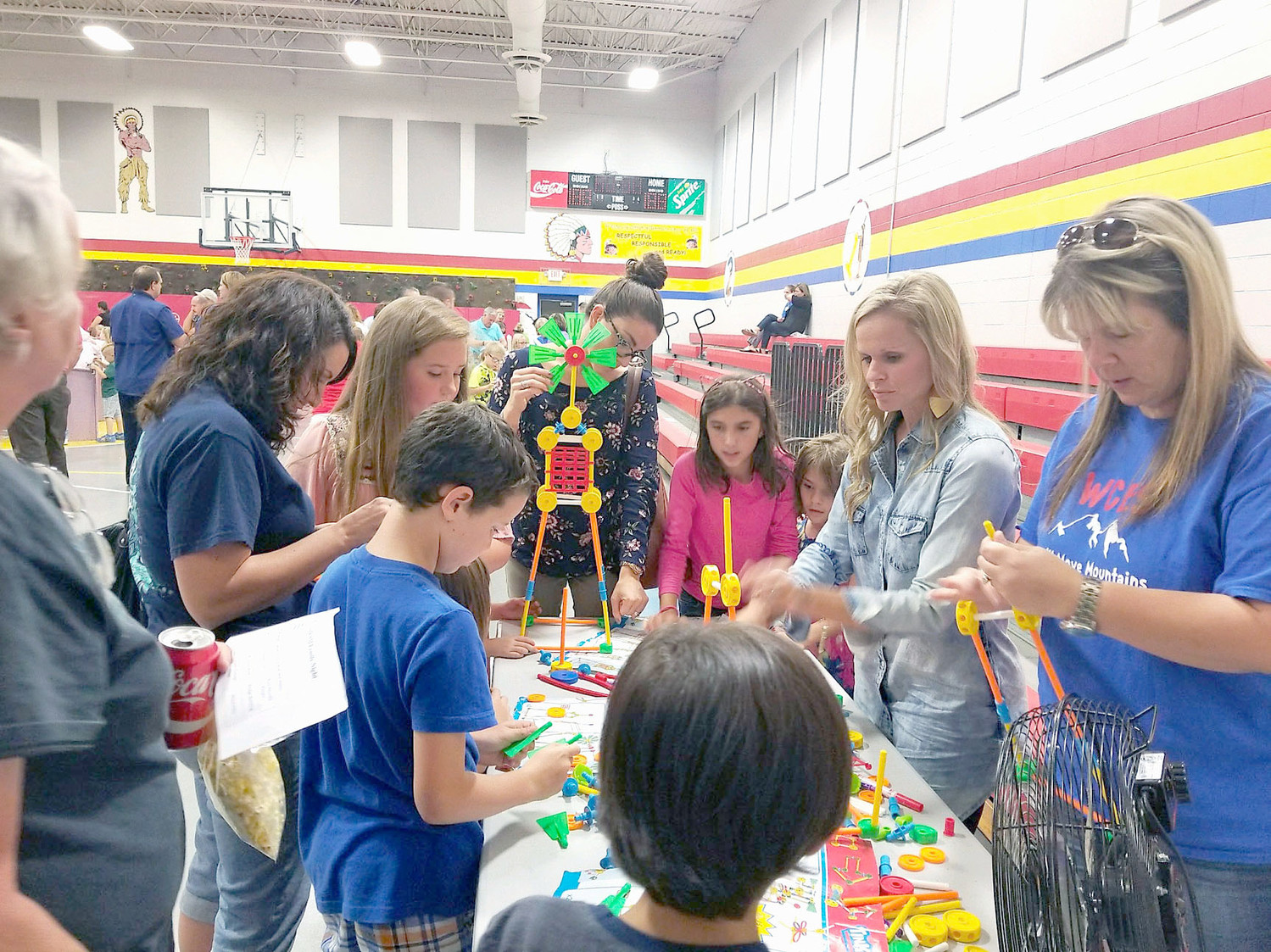 CREATING windmills, students work on a project using K'nex kits, with help from Rebecca Bacon and Kristi Conner. This was one of the nine stations available at STEAM Family Night at Waterville Community Elementary.